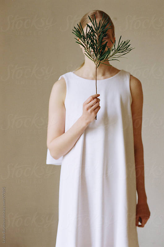 Young woman hides her face with a green branch by Lyuba Burakova for Stocksy United