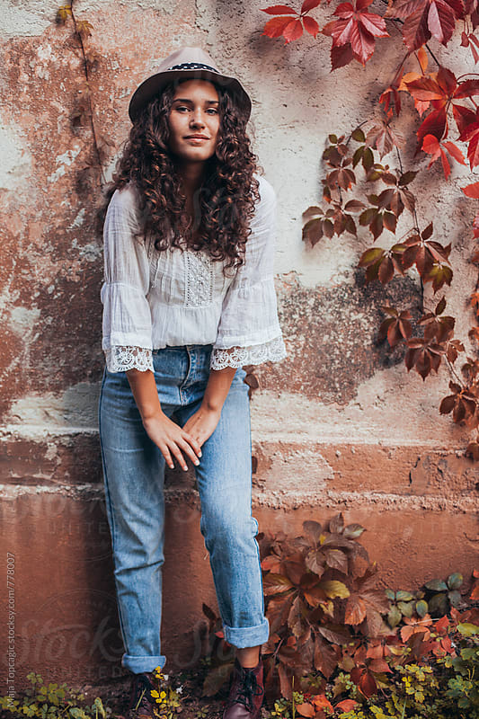 Beautiful young woman with curly hair, blue eyes and freckles by Maja Topcagic for Stocksy United