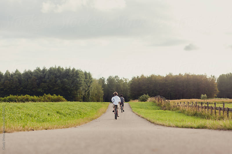 The backs of two boys on bicycles riding on a country road by Cindy Prins for Stocksy United