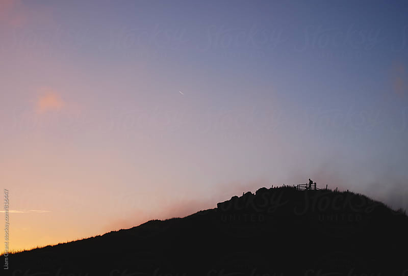 Male silhouetted on mountain top at sunset. Derbyshire, UK by Liam Grant for Stocksy United