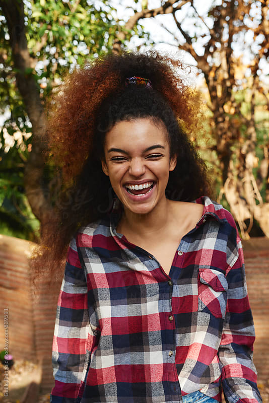 young afro woman laughing on the urban park by Guille Faingold for Stocksy United