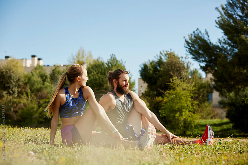 Woman With Male Instructor Doing Stretching Exercise In Park by ALTO IMAGES for Stocksy United