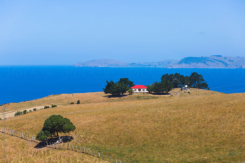 A small farm over a hill on the sea coast by Leandro Crespi for Stocksy United