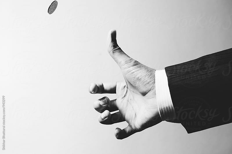 Hand of a businessman tossing a coin. by Shikhar Bhattarai for Stocksy United