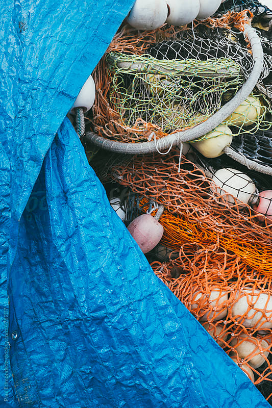 Blue tarpaulin covering pile of commercial fishing nets by Paul Edmondson for Stocksy United
