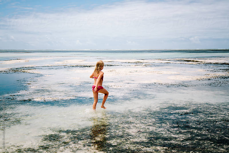 A little girl exploring a Zanzibar beach at low tide. by Helen Rushbrook for Stocksy United