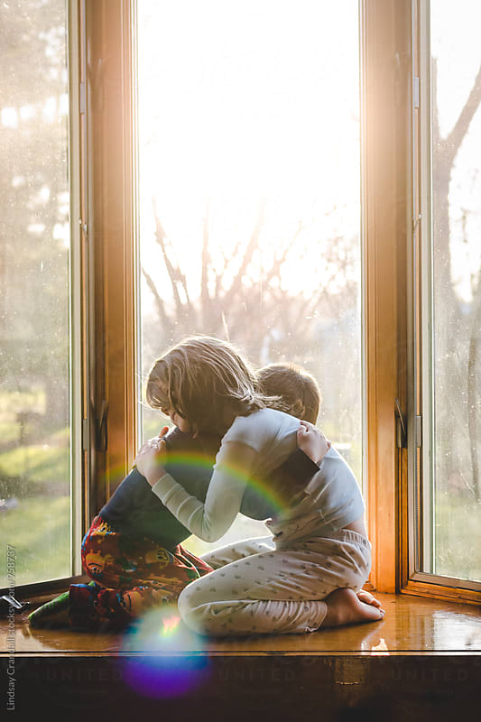 Two children hugging in the morning light by Lindsay Crandall for Stocksy United