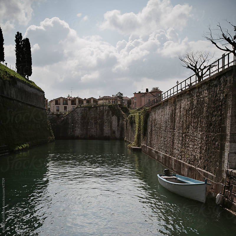 Canal with boat at Peschiera del Garda - Italy by Robert Kohlhuber for Stocksy United