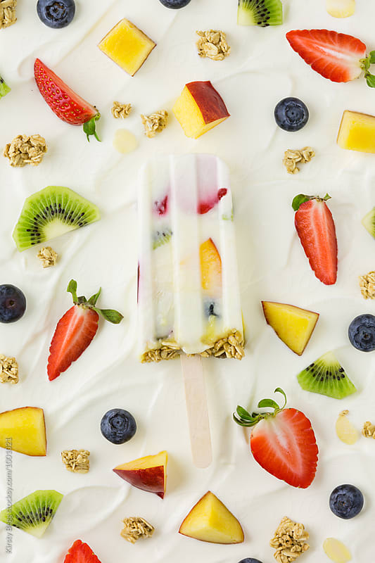 Yogurt parfait ice lolly on greek yogurt and fruit background by Kirsty Begg for Stocksy United