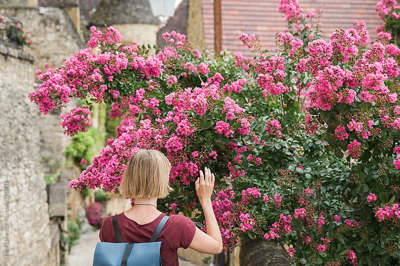 Young blond woman touching pink flowers on a bush by Lior + Lone for Stocksy United
