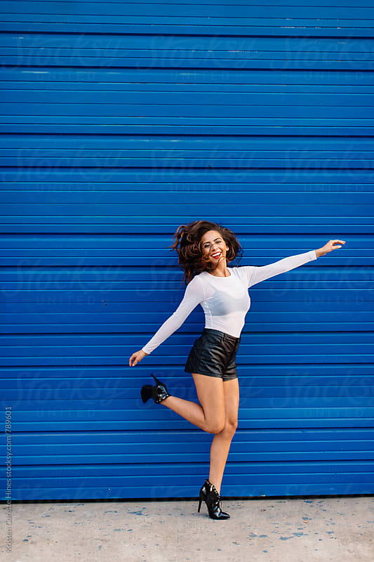 Happy woman in shorts and heels  by Kristen Curette Hines for Stocksy United