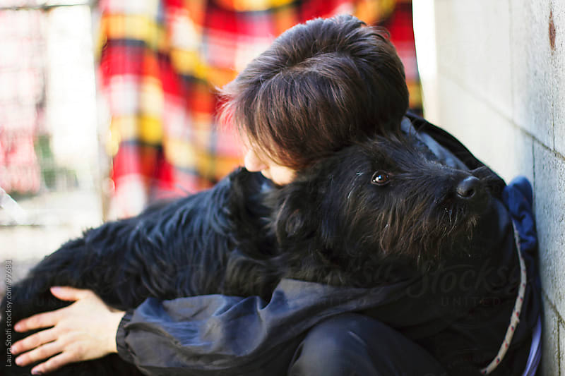 Portrait of woman hugging a giant Schnauzer dog looking at the camera by Laura Stolfi for Stocksy United