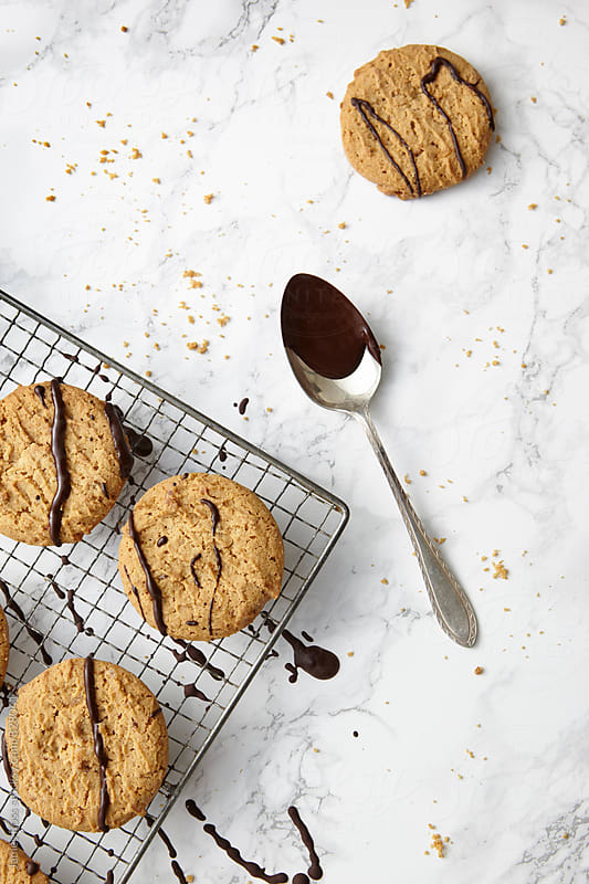 Ginger biscuits with dripped chocolate by James Ross for Stocksy United