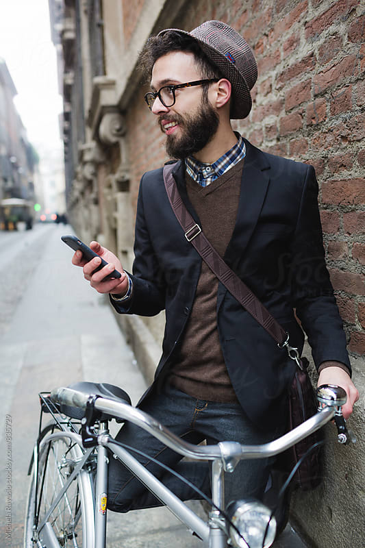 Smiling man using his mobile phone outdoors by michela ravasio for Stocksy United