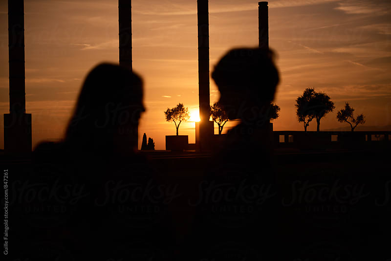 Unfocused silhouette of couple against of beautiful sunset by Guille Faingold for Stocksy United