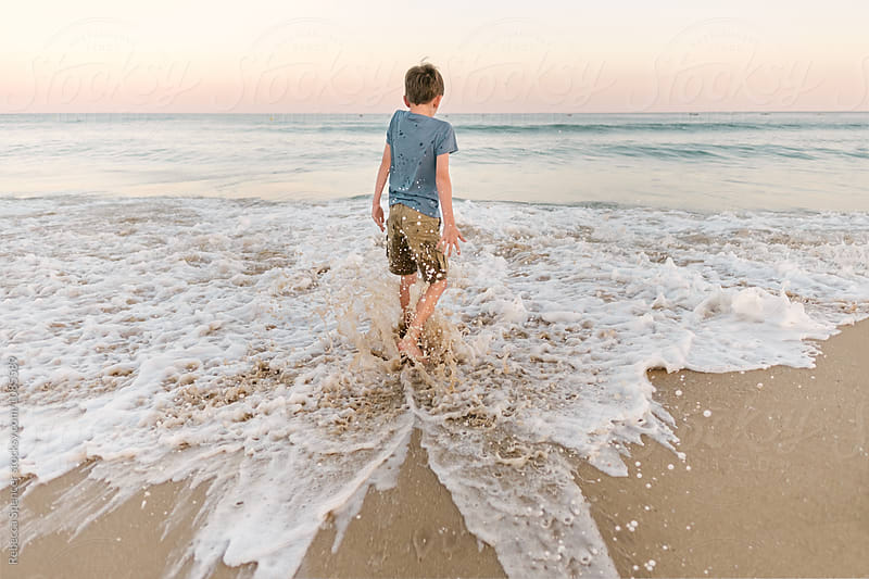 Waves splash over a boy wearing summer clothes by Rebecca Spencer for Stocksy United