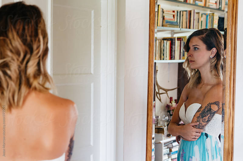young female with tattoos looking in mirror wearing dress by Jesse Morrow for Stocksy United