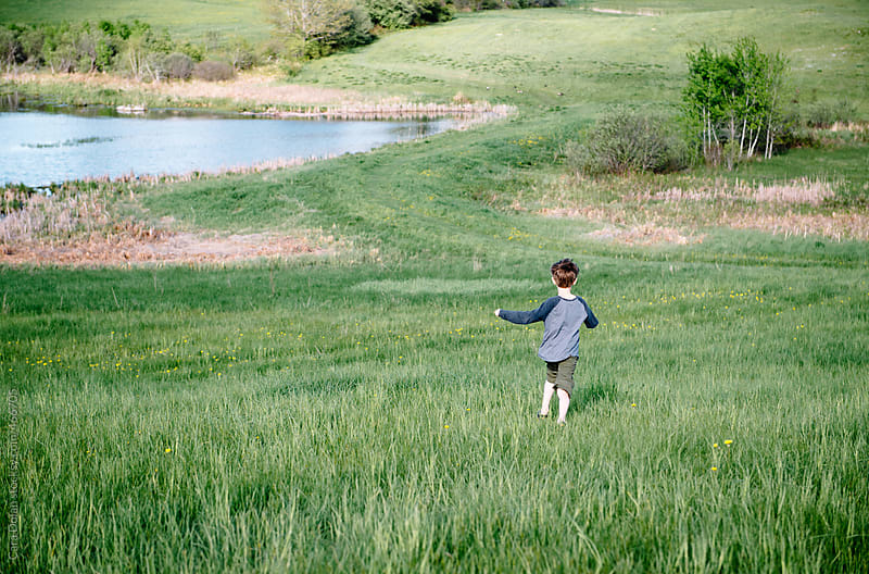 Child runs through a meadow in summertime by Cara Dolan for Stocksy United