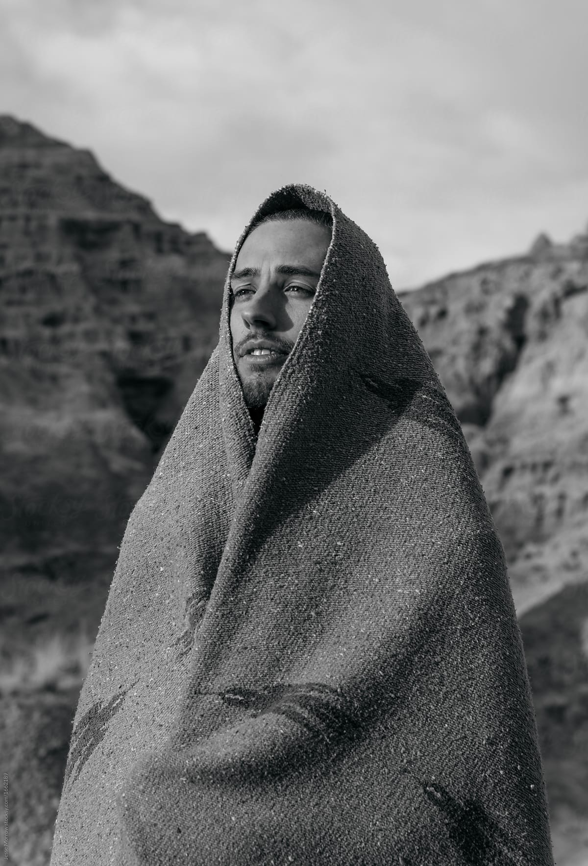 Black and White Lifestyle portrait of young adult male wearing tribal  blanket in high desert unique