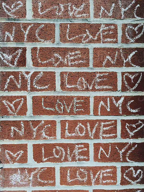 Chalk graffiti writing on a wall in a city, Love, NYC and hearts by Greg Schmigel for Stocksy United