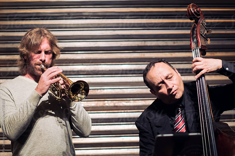 Jazz performance of two trumpet and double bass musicians by Per Swantesson for Stocksy United