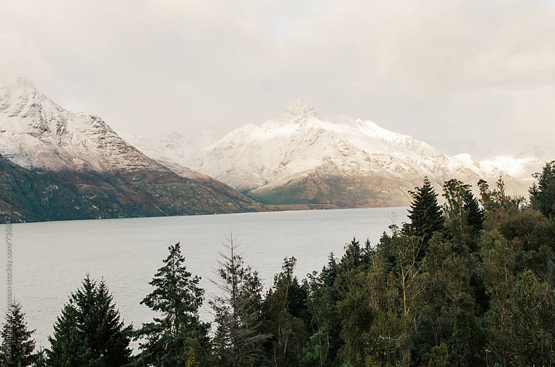Snow falling on mountain by a lake by Dominique Chapman for Stocksy United