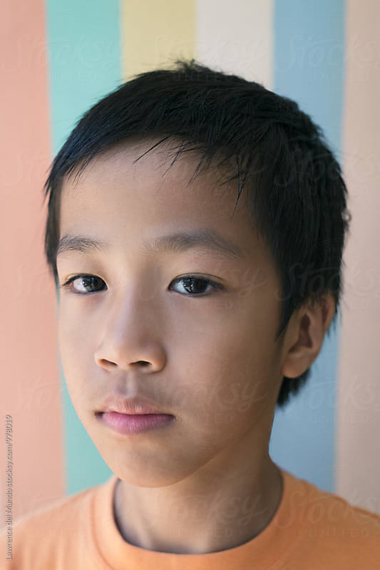 Portrait of a thoughtful young 9 year old boy against a pastel background by Lawrence del Mundo for Stocksy United