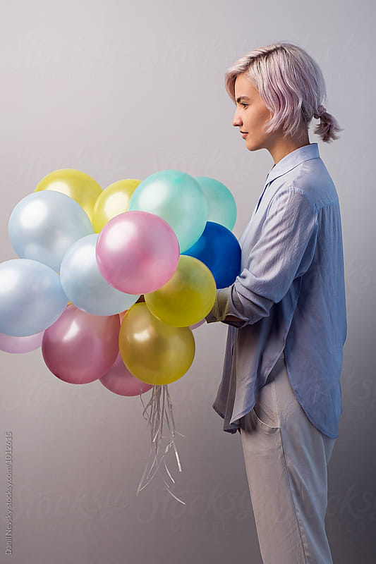 Side view of young girl holding bunch of colorful balloons by T-REX & Flower for Stocksy United