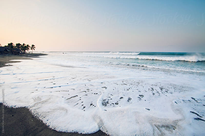 Waves washing over the sand at high tide by Denni Van Huis for Stocksy United