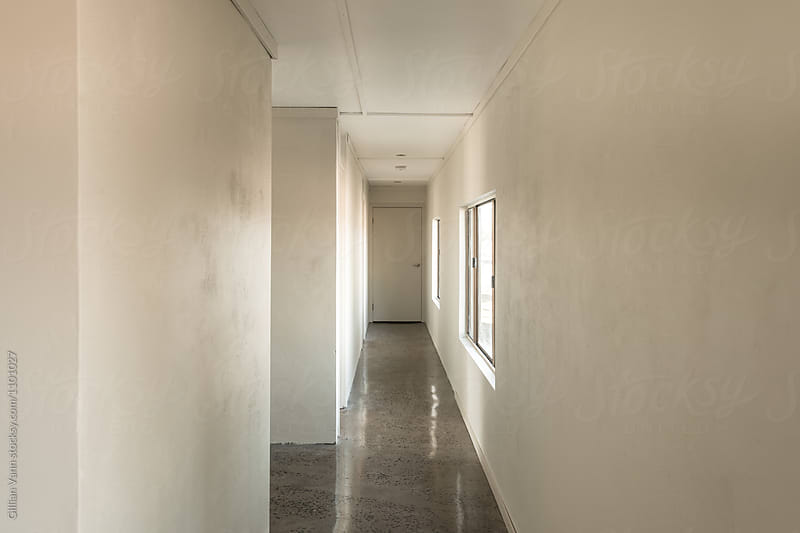 dormitary style accommodation, empty hallway leading to bedrooms by Gillian Vann for Stocksy United