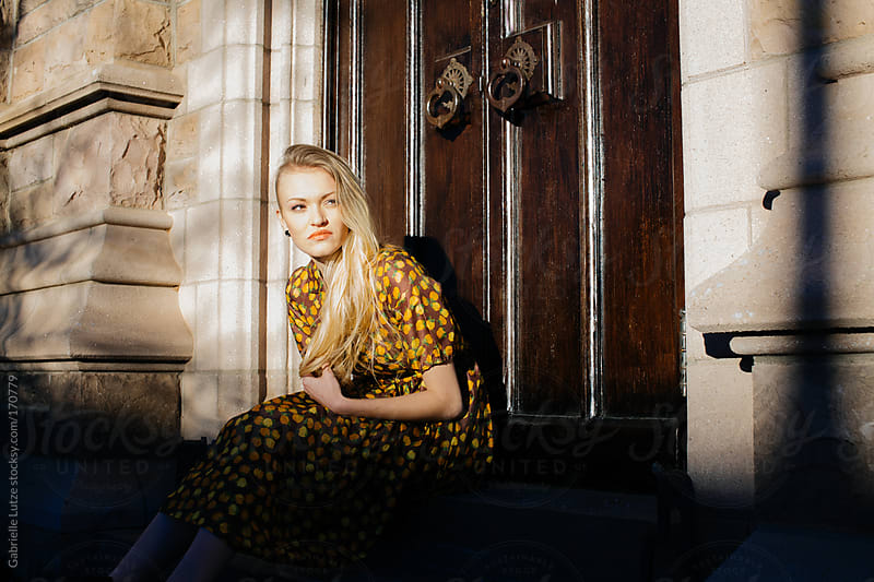 Beautiful Girl in Vintage Dress Sitting by an Old Door by Gabrielle Lutze for Stocksy United