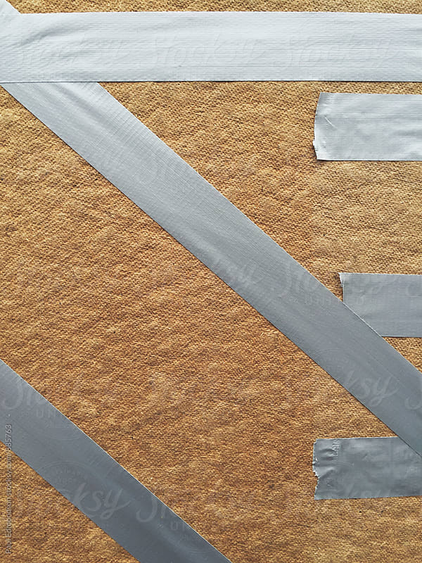Duct tape across wood panel, covering broken shop window by Paul Edmondson for Stocksy United