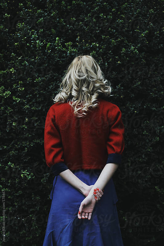 Young woman standing in front of bush  by Jovana Rikalo for Stocksy United