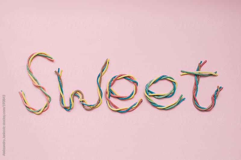 Gummy worms candy on the pink background by Aleksandra Jankovic for Stocksy United