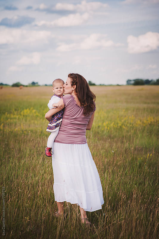 Mother holding her baby daughter in her arms walking on an open field  by Lea Csontos for Stocksy United