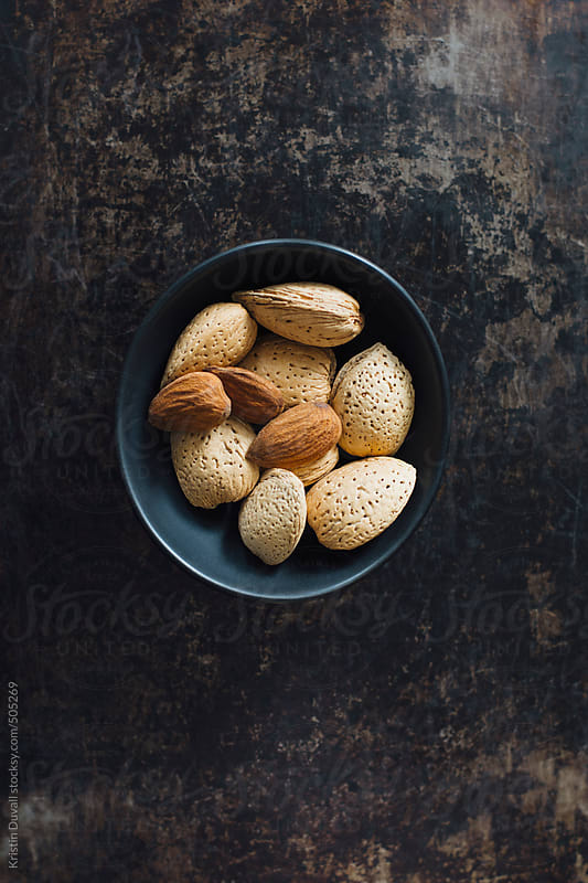 Whole and shelled almonds in bowl by Kristin Duvall for Stocksy United