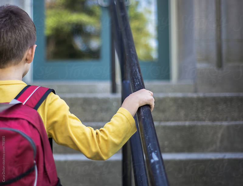 Boy in red backpack holds railing as he walks up the school steps by Cara Dolan for Stocksy United