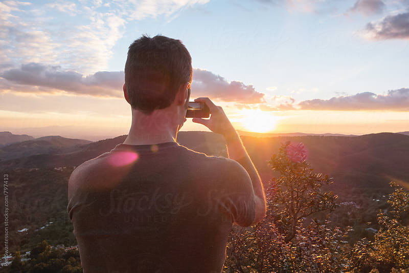 Young man taking a cell phone photo of the sunset by Per Swantesson for Stocksy United