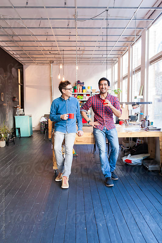 A team of two professionals or entrepeneurs drinking coffee in their office, looking at the camera by Ivo de Bruijn for Stocksy United