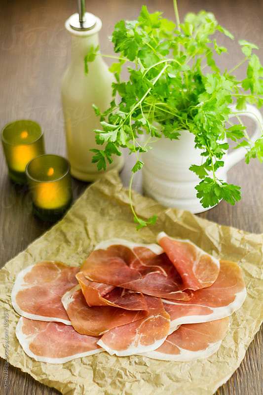 Prosciutto on paper with parsley by Kirsty Begg for Stocksy United