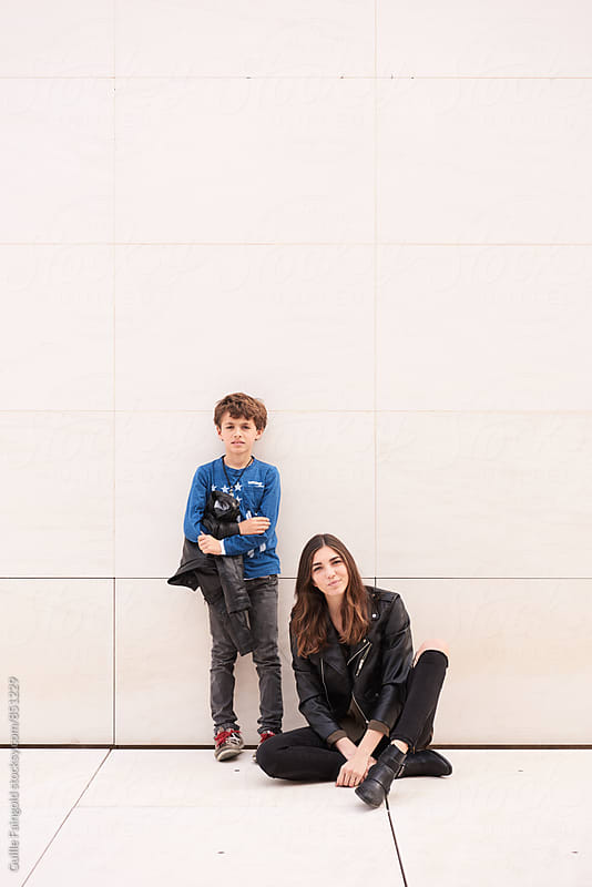 Sister and brother against of urban wall by Guille Faingold for Stocksy United
