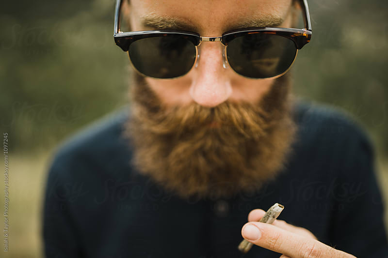 Young Man Smoking by Isaiah & Taylor Photography for Stocksy United