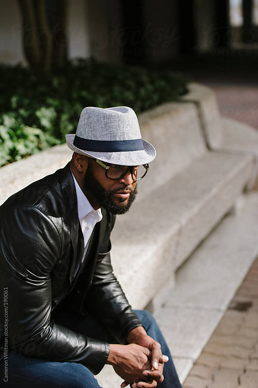 Stylish, bearded black man relaxing in a city space  by Cameron Whitman for Stocksy United