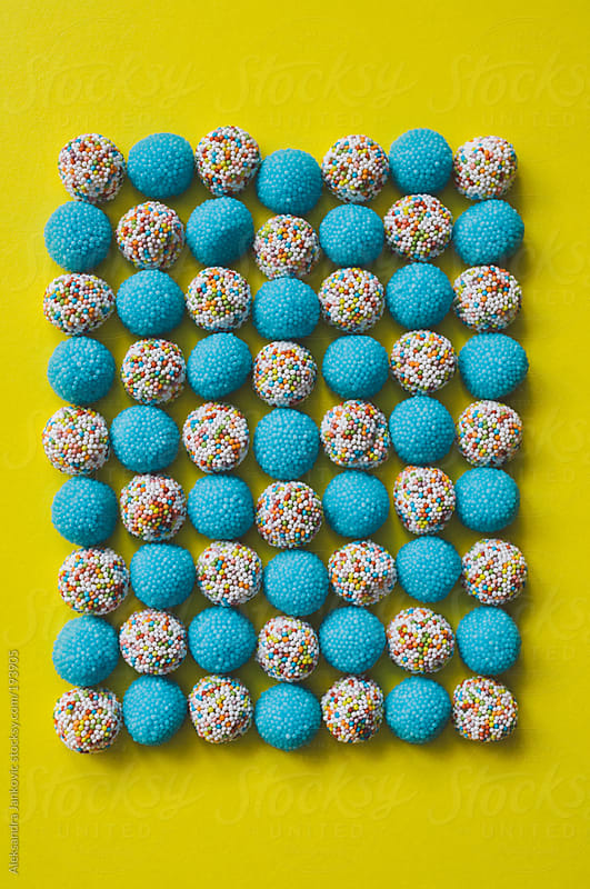 Colorful gummies on the yellow background by Aleksandra Jankovic for Stocksy United