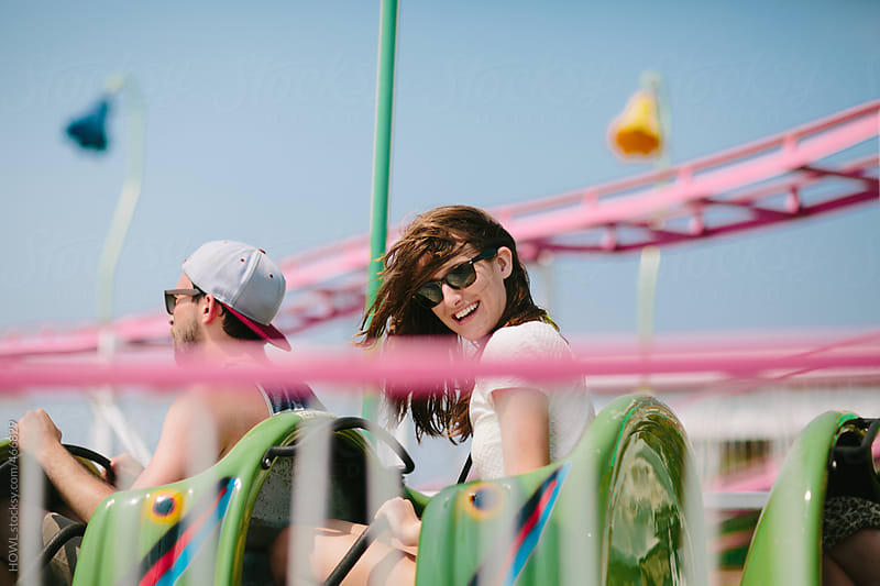 Youthful girl in sunglasses rides a roller coaster in the summer  by HOWL for Stocksy United