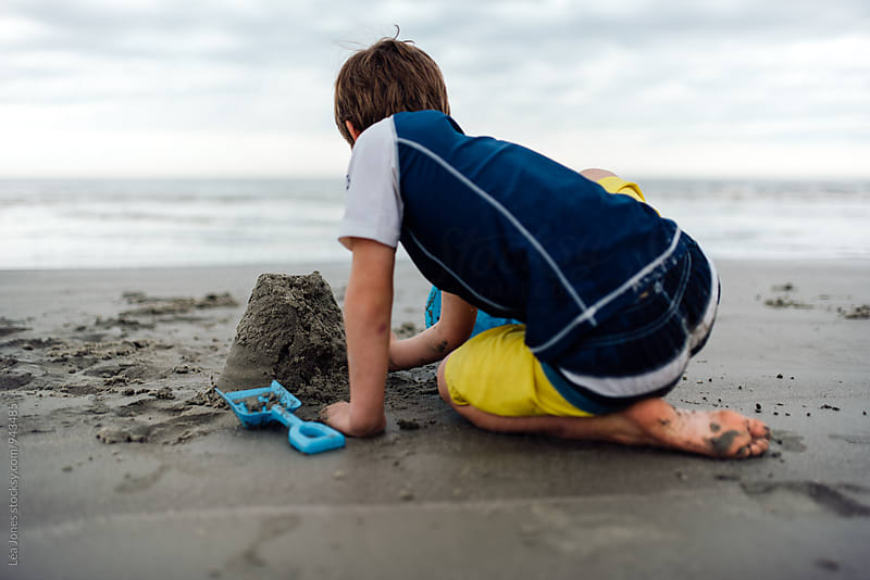 boy building a sandcastle on the beach by Léa Jones for Stocksy United
