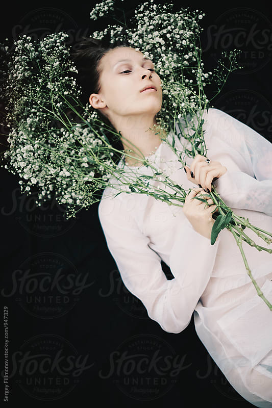 Girl holding white flowers and lying in a black background by Sergey Filimonov for Stocksy United