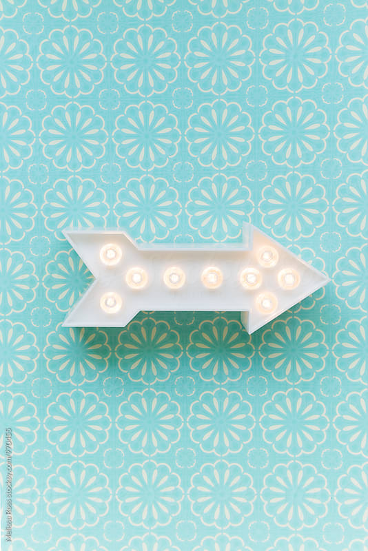 Arrow marquee light on a patterned background by Melissa Ross for Stocksy United