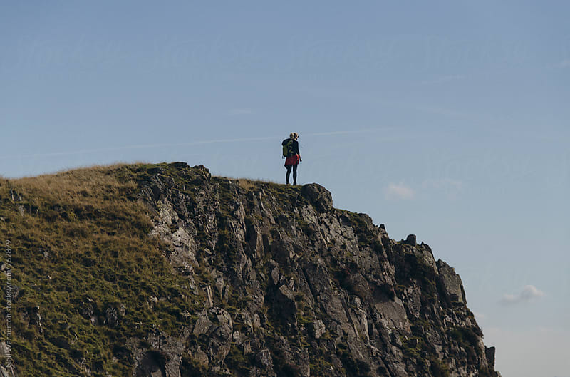 Hiker taking in the view from a cliff edge by Neil Warburton for Stocksy United