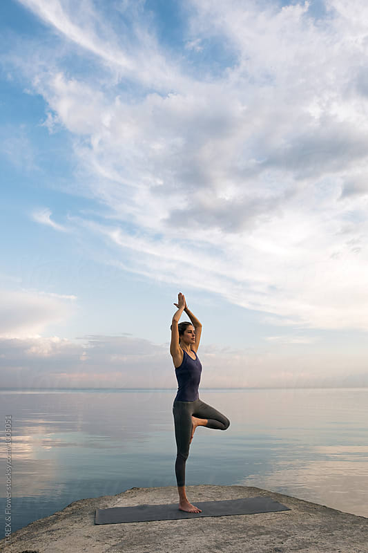 Portrait of young woman in tree pose at waterfront by Danil Nevsky for Stocksy United